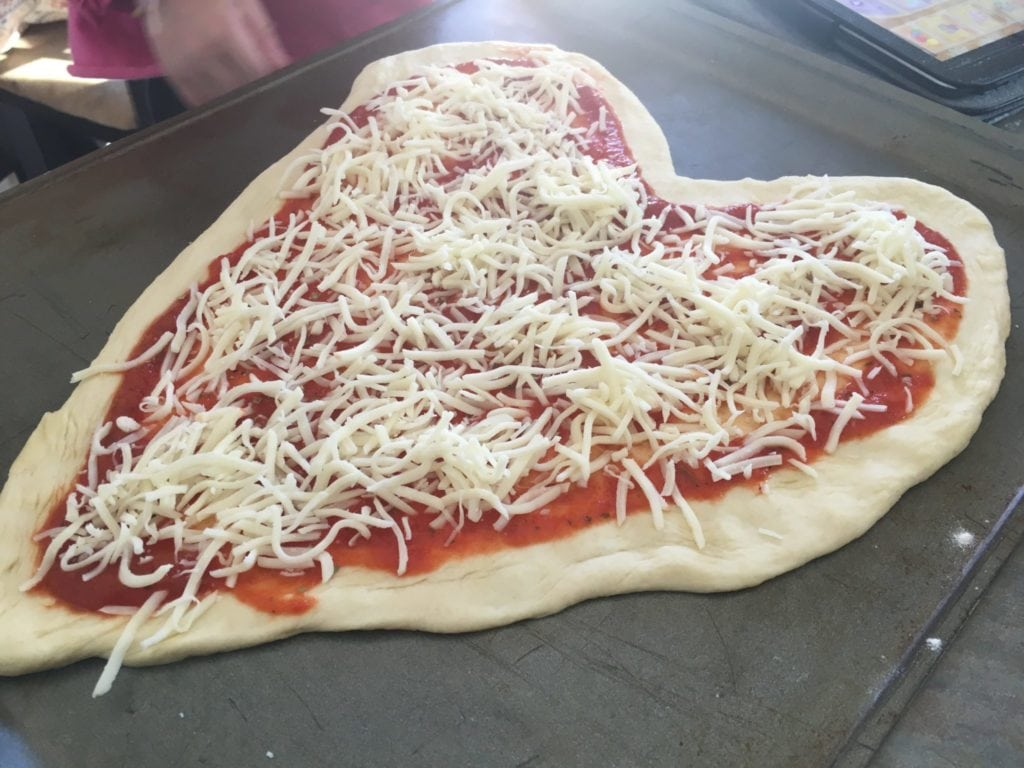 sprinkling cheese on heart shaped pizza